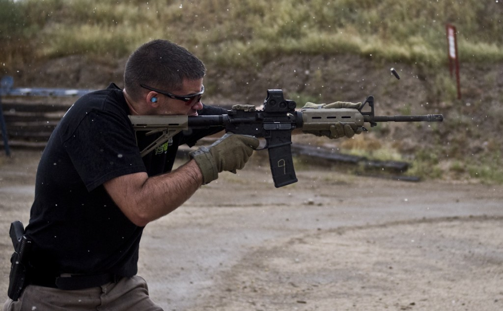 A man fires an AR-15 during with heavy raindrops falling.